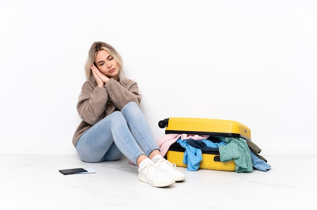 Mujer joven sentada en el piso con maleta