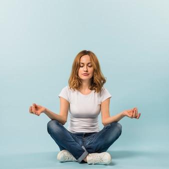 Mujer joven sentada en el piso mediando contra el fondo azul