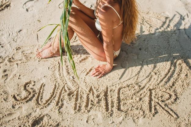 Mujer joven sentada en la playa de arena bajo la hoja de palmera