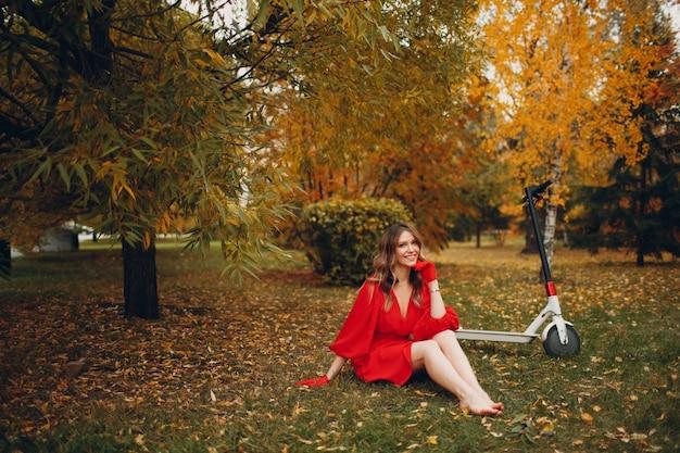 Mujer joven sentada con scooter eléctrico en vestido rojo en el parque de la ciudad de otoño