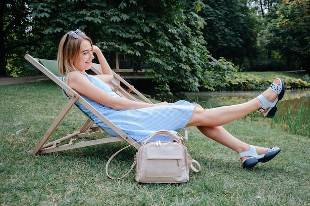 Mujer joven sentada en una silla de camping en el parque
