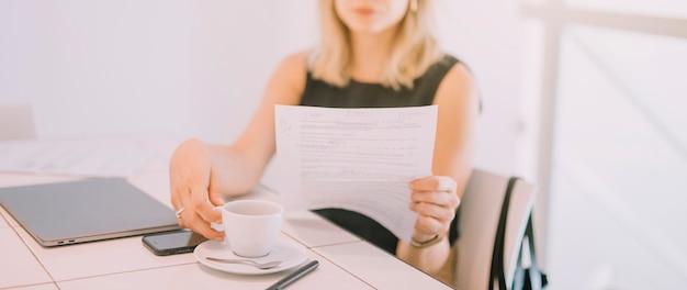 Mujer joven sentada en una silla leyendo el documento tomando el café en el lugar de trabajo
