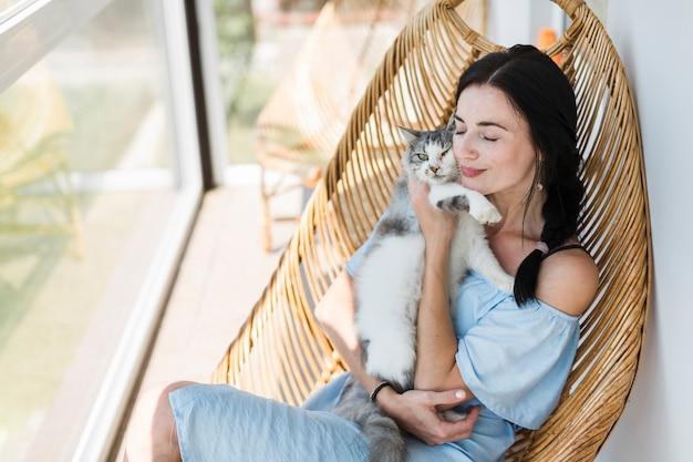 Mujer joven sentada en una silla en el patio amando a su gato mascota