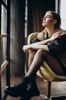 Mujer joven sentada en una silla sola
