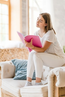 Mujer joven sentada en el sofá leyendo el libro rosa en casa