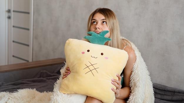 Mujer joven sentada en el sofá y pensando. hermosa chica sosteniendo cojín y mirando serio o triste
