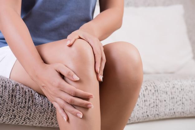 Mujer joven sentada en el sofá y sentir dolor de rodilla.