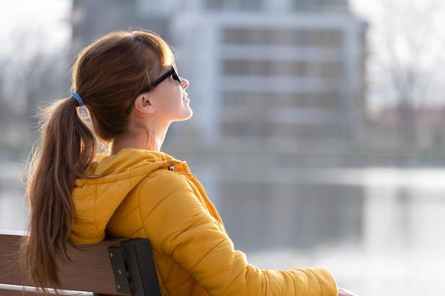 Mujer joven sentada sola en un banco del parque relajante en un cálido día de otoño.