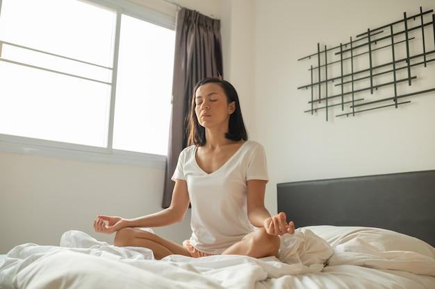 Mujer joven sentada en su cama en el dormitorio y meditando.