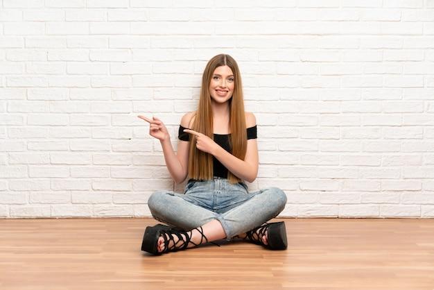 Mujer joven sentada en el suelo apuntando el dedo hacia el lado