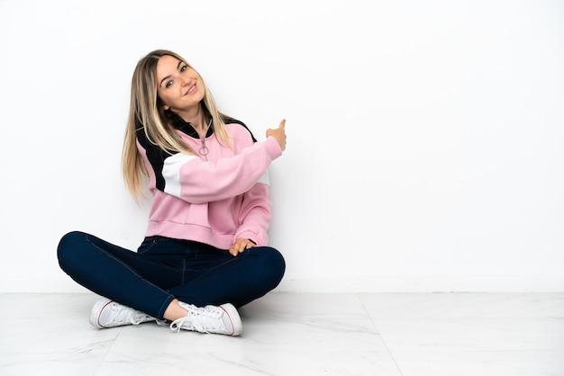 Mujer joven sentada en el suelo en el interior apuntando hacia atrás