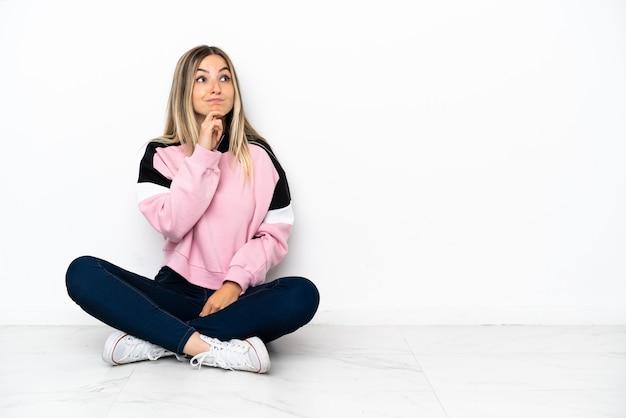 Mujer joven sentada en el suelo en el interior teniendo dudas y pensando