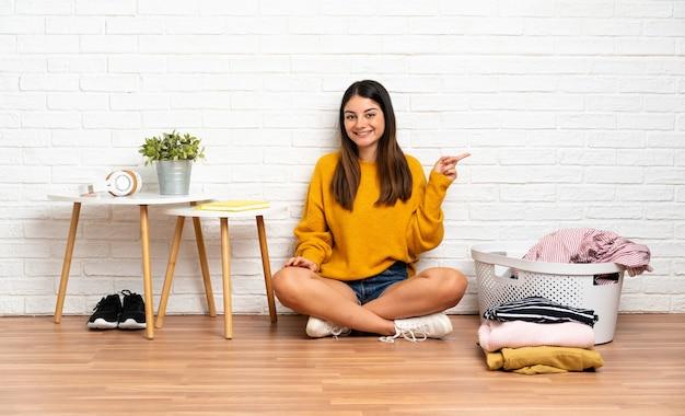 Mujer joven sentada en el suelo en interiores con cesta de ropa apuntando con el dedo hacia un lado y presentando un producto