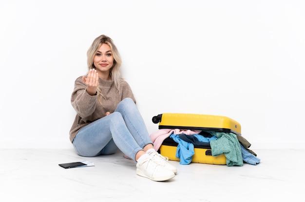 Mujer joven sentada en el suelo con maleta sobre aislado