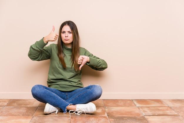 Mujer joven sentada en el suelo mostrando los pulgares hacia arriba y hacia abajo, difícil elegir el concepto