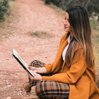 Mujer joven sentada en el suelo con las piernas cruzadas leyendo el libro