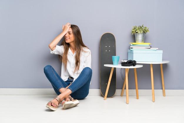 Mujer joven sentada en el suelo que tiene dudas con expresión de la cara confusa
