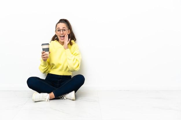 Mujer joven sentada en el suelo sosteniendo un café para llevar gritando con la boca abierta