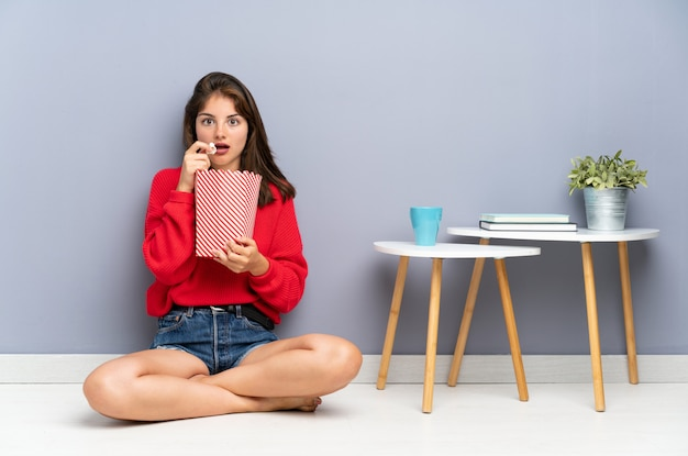 Mujer joven sentada en el suelo y sosteniendo palomitas de maíz