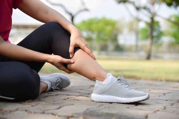 Mujer joven sentada en el suelo y sufriendo lesiones en la pierna. mujer sosteniendo su pierna debido a esguince.