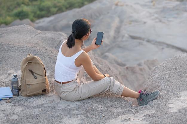 Mujer joven sentada con teléfono móvil. ruta turística de alta montaña al atardecer.