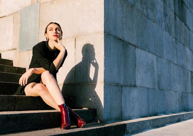 Mujer joven, sentado, en, escalera, en, luz del sol