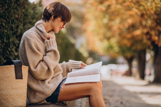 Mujer joven, sentado, en el estacionamiento, y, lectura