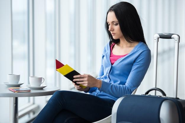 La mujer joven se está sentando en el aeropuerto con café.