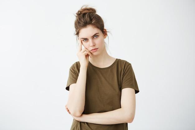 Mujer joven seria con bollo pensando