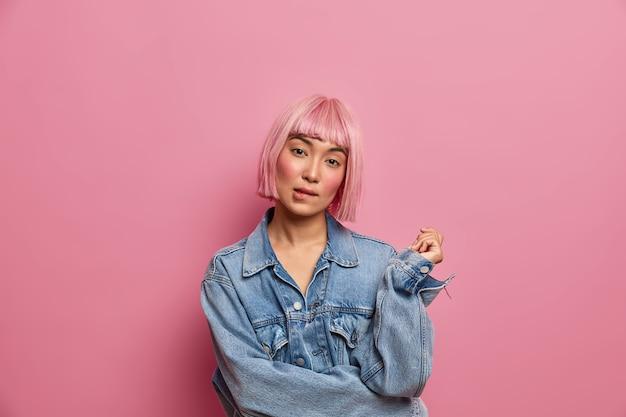 Una mujer joven seria y de moda inclina la cabeza y se muerde los labios, intenta pensar en una solución, tiene dudas sobre algo, usa una elegante chaqueta de mezclilla, tiene el cabello rosado de moda. concepto de expresiones faciales
