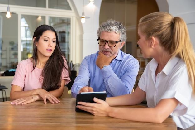 Mujer joven seria pensativa y hombre maduro reunidos con mujeres profesionales, viendo y discutiendo contenido en tableta