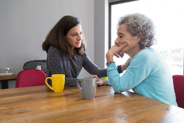 Mujer joven seria que consuela a su madre senior molesta