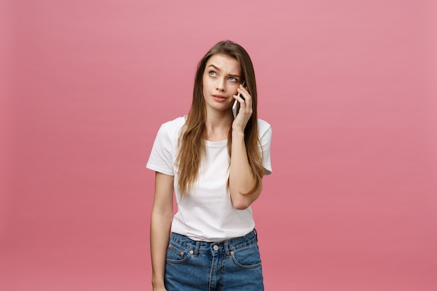 Mujer joven seria que habla en el teléfono aislado en rosa.