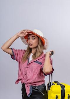 Una mujer joven seria vistiendo camisa roja con maleta amarilla mientras mira en una pared blanca