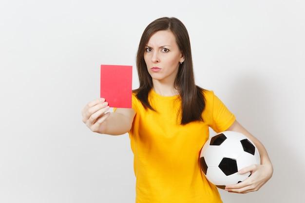 Mujer joven severa seria europea, árbitro de fútbol o jugador en uniforme amarillo que muestra la tarjeta roja, sosteniendo un balón de fútbol aislado sobre fondo blanco. deporte, jugar al fútbol, concepto de estilo de vida saludable.