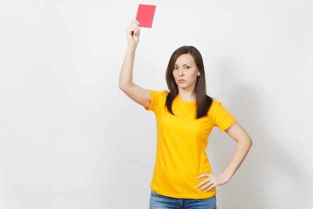 Mujer joven severa seria europea, árbitro de fútbol en uniforme amarillo mostrar tarjeta de fútbol roja, proponer que el jugador se retire del campo aislado sobre fondo blanco. deporte, juego, concepto de estilo de vida saludable.