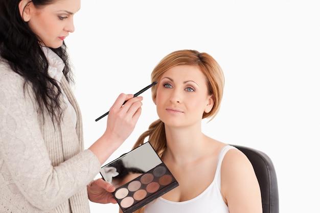 Mujer joven siendo compuesta por un artista de maquillaje
