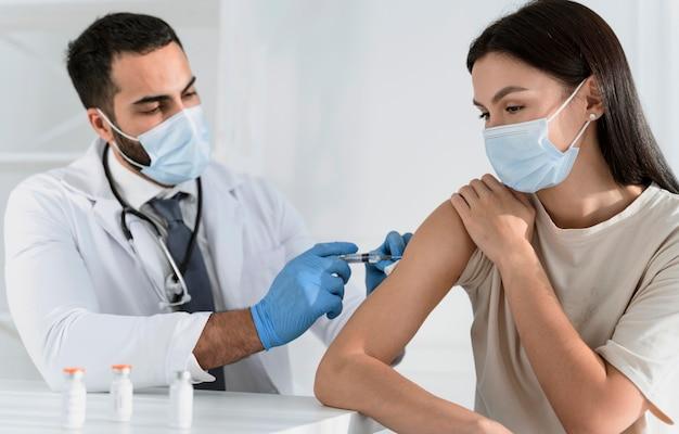 Mujer joven siendo vacunada por médico