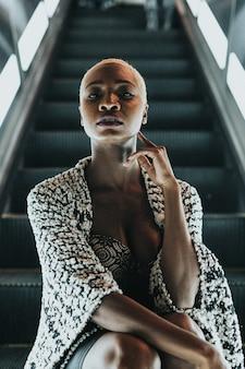 Mujer joven, se sienta, en, escalera mecánica