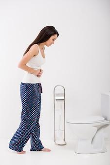 Mujer joven se siente mal en el baño.