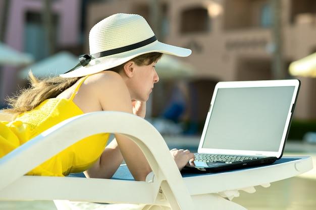 Mujer joven en silla de playa en la piscina trabajando en equipo portátil conectado a internet inalámbrico escribiendo texto en las teclas en el lugar de veraneo. trabajo a distancia y trabajo independiente mientras viaja concepto.