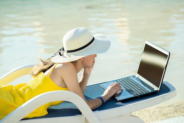 Mujer joven en silla de playa en la piscina trabajando en equipo portátil