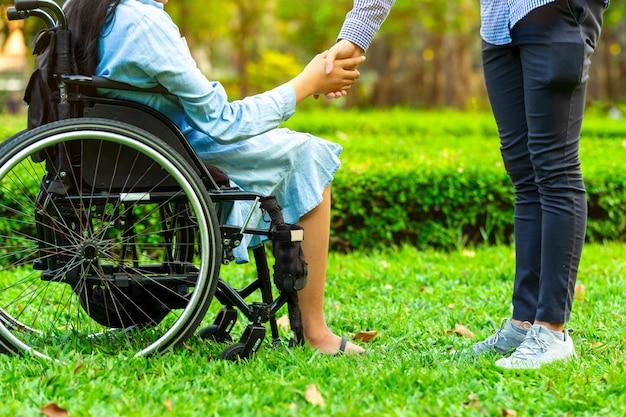 Mujer joven en la silla de ruedas que lleva a cabo las manos con el hombre del cuidador en parque público.