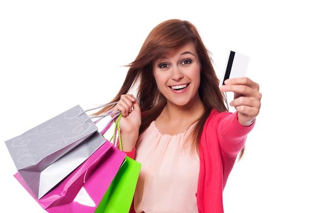 Mujer joven sincera mostrando tarjeta de crédito y sosteniendo bolsas de la compra.