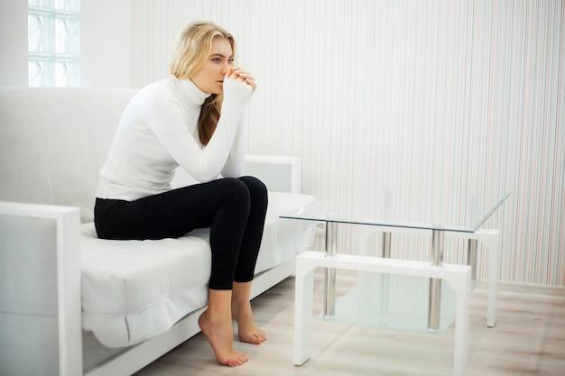 Mujer joven sintiéndose deprimida en casa