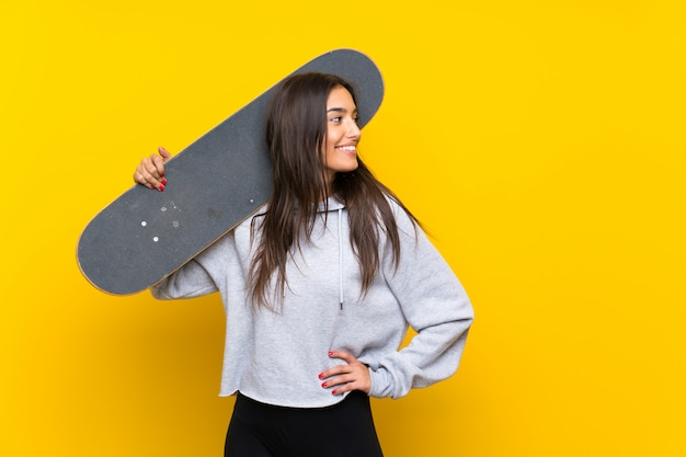 Mujer joven skater sobre pared amarilla aislada