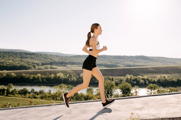 Mujer joven slim fit corriendo al aire libre por la mañana