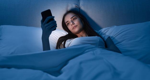 Mujer joven con smartphone acostado en la cama