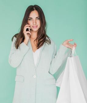 Mujer joven con smartphone y bolsas de compras