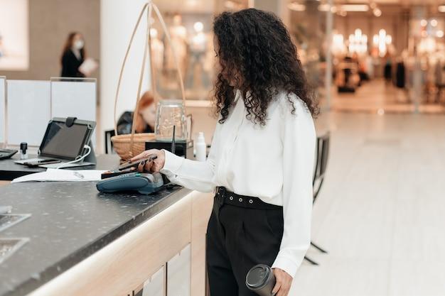 Mujer joven con un smartphone de pie en una cafetería de supermercado